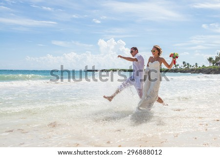 Couple Running Through Waves On Beach Holiday. - stock photo