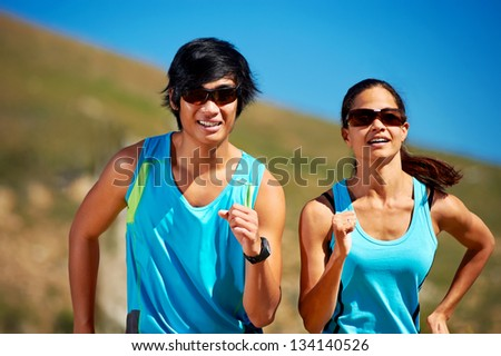 couple running together training for marathon and fitness - stock photo