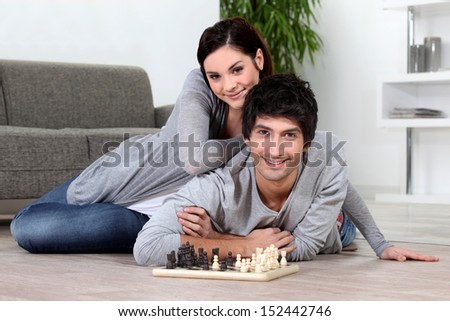 Couple sat at home playing chess - stock photo