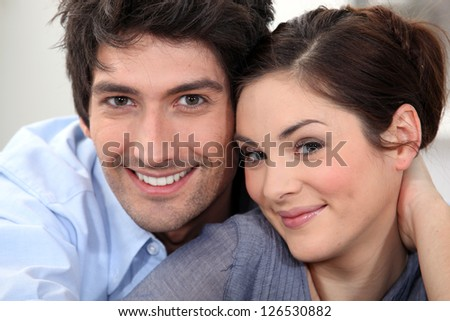 Couple sat hugging at home - stock photo