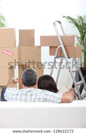 Couple sat on sofa in new house - stock photo