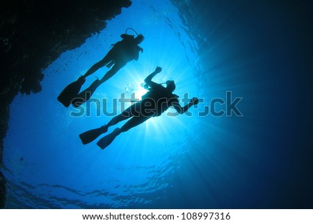 Couple Scuba Diving, silhouettes against sun