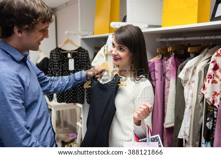 Couple selecting a dress while shopping for clothes in apparel shop