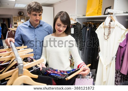Couple selecting a dress while shopping for clothes in apparel shop - stock photo