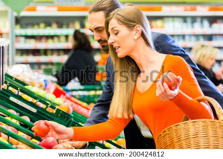 Couple selecting apples while grocery shopping in supermarket  - stock photo
