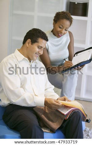 Couple Selecting Fabric From Swatch - stock photo