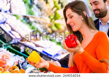 Couple selecting paprika while grocery shopping in supermarket  - stock photo