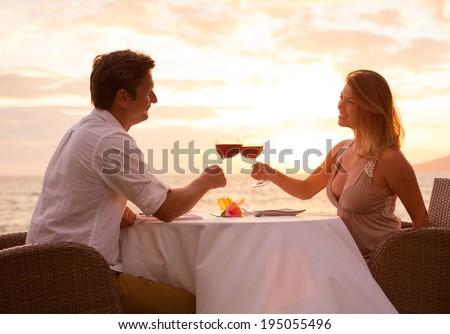Couple sharing romantic sunset dinner on the beach - stock photo