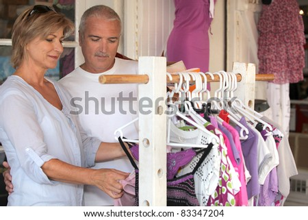 Couple shopping for women's clothes - stock photo