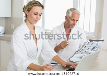 Couple shopping online and reading newspaper in bathrobes at home in the kitchen - stock photo