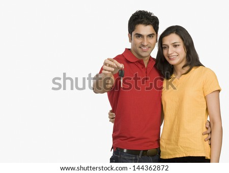 Couple showing a car key - stock photo