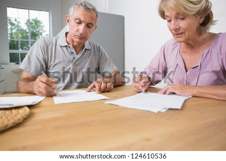 Couple signing documents together in the kitchen - stock photo