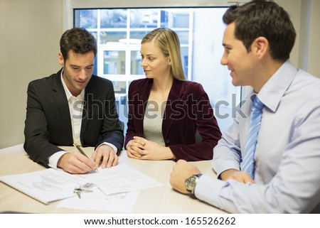 Couple signing real-estate contract - stock photo