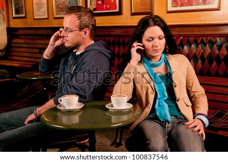 Couple siiting at a table over coffee giving one another the cold shoulder following a disagreement or altercation and sitting looking in opposite directions - stock photo