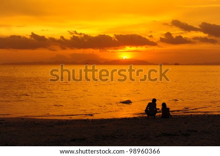 Couple Silhouette on Beach with Sunset Background - stock photo