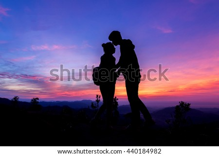 Couple silhouette on the mountains at twilight.