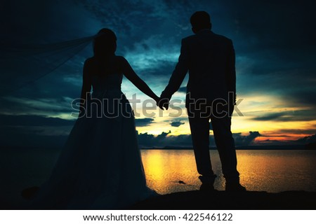 couple silhouettes holding hands and walking together looking each other in a date at sunset on the beach.with dark and low light style. - stock photo