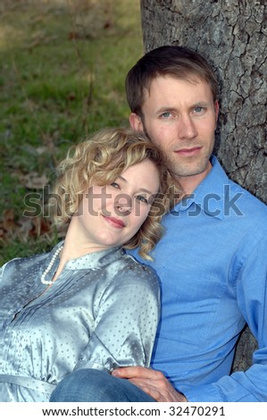 Couple sit close together against a tree trunk outdoors.  He is wearing a blue shirt and jeans and she a grey silk blouse. - stock photo