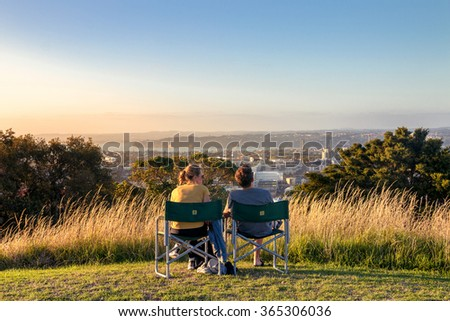 Couple Sit Together in the Sunset on Mount Eden, Auckland - stock photo