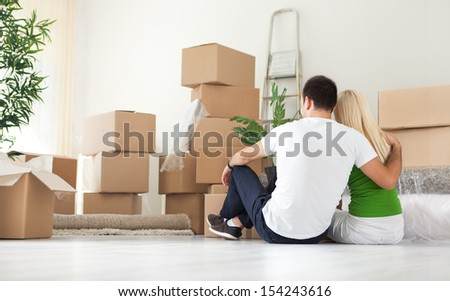 Couple sitting  and looking  lot of moving boxes, back view - stock photo