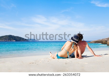 couple sitting and relaxing on the paradise beach during their honeymoon - stock photo