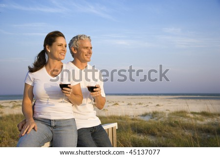 Couple sitting and relaxing together at the beach with glasses of red wine. Horizontal shot