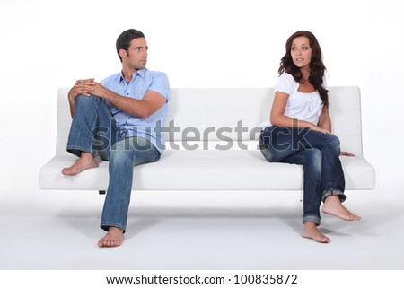 couple sitting apart in couch after quarrel - stock photo
