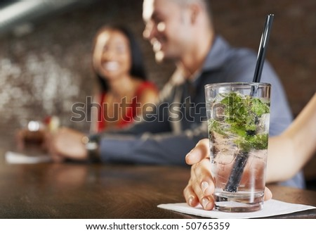 Couple sitting at bar, cocktail glass in foreground - stock photo