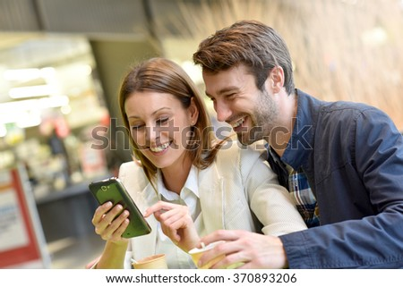 Couple sitting at coffee shop and using smartphone