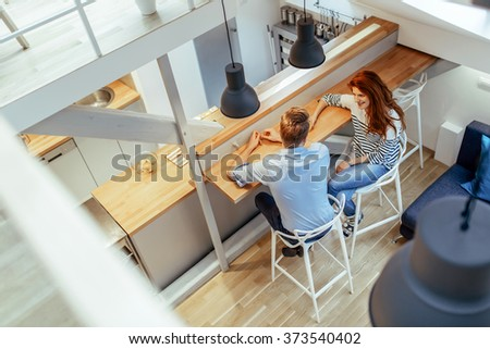 Couple sitting at counter in a nicely decorated clean home - stock photo