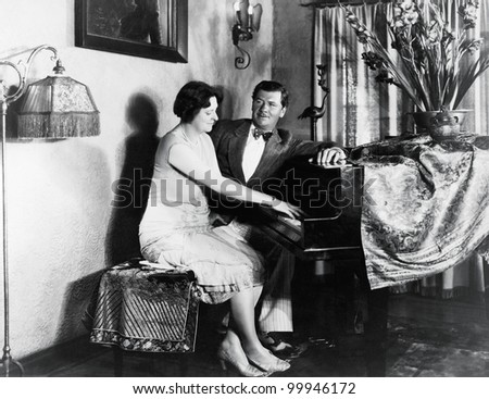 Couple sitting at piano - stock photo
