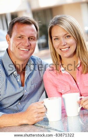 Couple sitting at sidewalk caf - stock photo