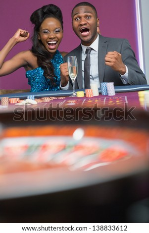Couple sitting at the table cheering at roulette wheel spinning in the casino - stock photo