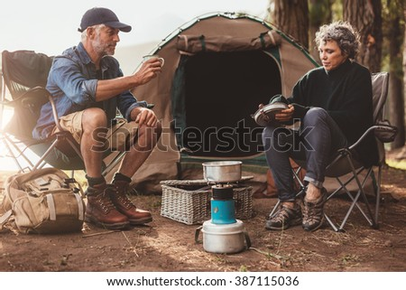 Couple sitting at their campsite, with man drink coffee. Senior couple camping in nature. - stock photo