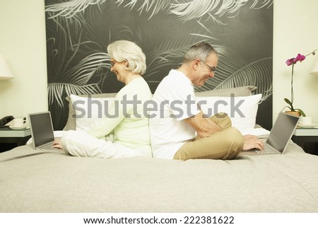 Couple Sitting Back to Back on Bed in Hotel Room Using Their Laptops - stock photo