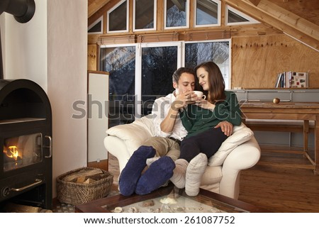 Couple sitting by fireplace and drinking tae - stock photo