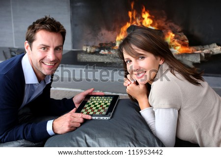 Couple sitting by fireplace and playing game with tablet - stock photo