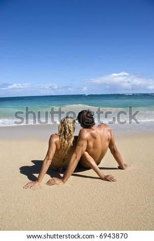 Couple sitting close together on Maui, Hawaii beach looking out at ocean.