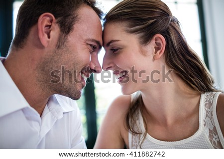 Couple sitting face to face in a restaurant on a date - stock photo