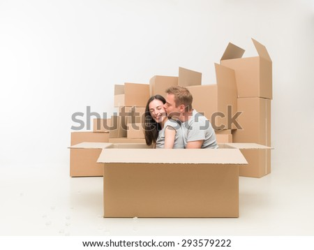 couple sitting in a box, kissing and having fun after moving in new home - stock photo