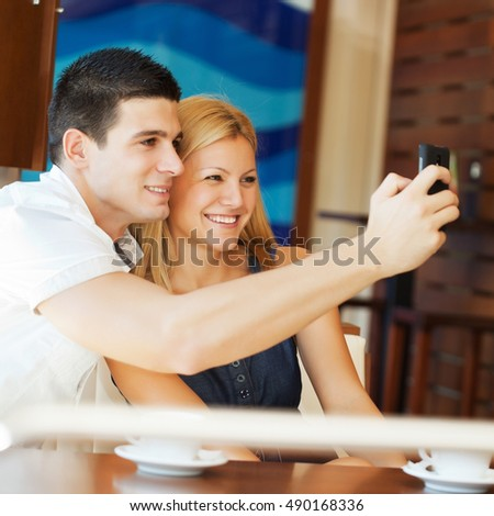 Couple sitting in cafe and taking a picture with mobile phone.
