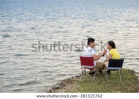 Couple sitting in camping chairs by the lake and enjoying date
