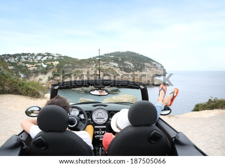 Couple sitting in convertible car and looking at panorama - stock photo