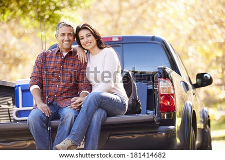 Couple Sitting In Pick Up Truck On Camping Holiday - stock photo