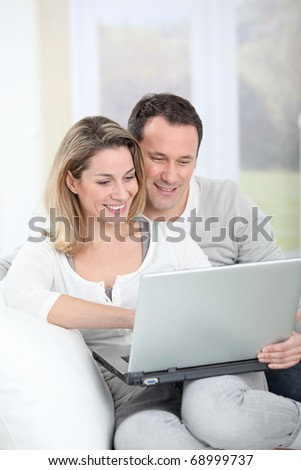 Couple sitting in sofa with laptop computer - stock photo