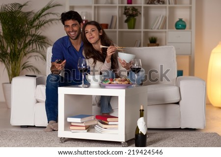 Couple sitting in the living room, watching TV. - stock photo