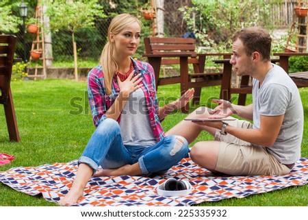 Couple sitting on a blanket with tablet pc at summer green park. They are arguing. - stock photo