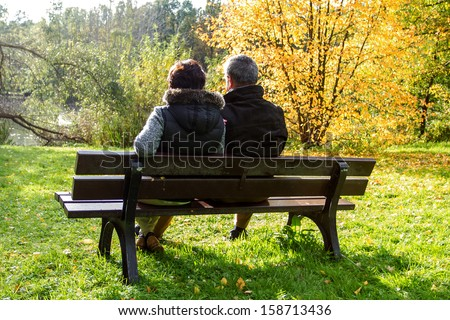 Couple sitting on a park bench in the autumn sun - stock photo