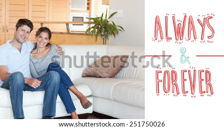 Couple sitting on a sofa against always and forever - stock photo