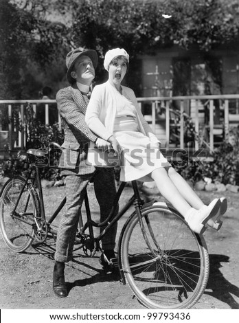 Couple sitting on a tandem bicycle - stock photo